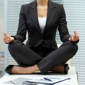 Image of young employer on workplace and meditating